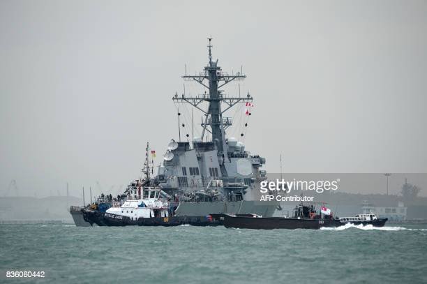 The guidedmissile destroyer USS John S McCain is guided by a tugboat after a collision with an oil tanker outside Changi naval base in Singapore on...