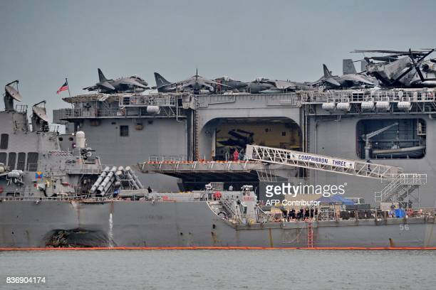 The guidedmissile destroyer USS John S McCain seen with a hole on its portside after a collision with a tanker docks next to the USS America at...