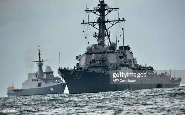 TOPSHOT The guidedmissile destroyer USS John S McCain with a hole on its portside after a collision with an oil tanker is escorted by Singapore Navy...