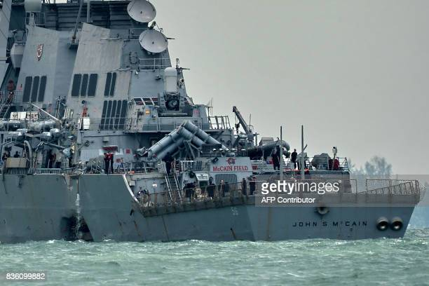 The guidedmissile destroyer USS John S McCain with a hole on its portside after a collision with an oil tanker makes its way to Changi naval base in...