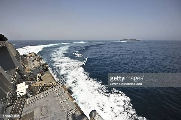 The guidedmissile destroyer USS Porter DDG 78 performs a flankspeed maneuver after completing a vertical replenishment with the Military Sealift...