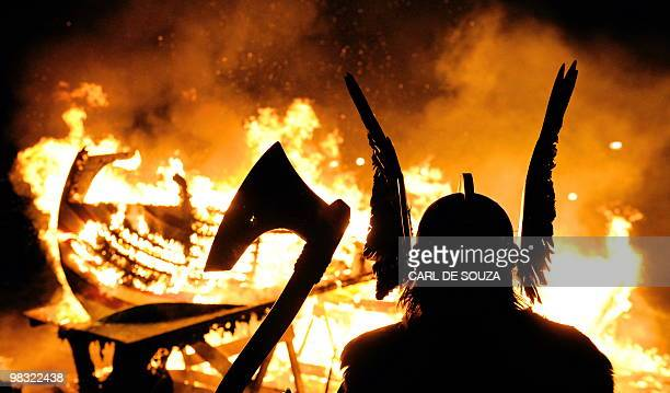 The Guizer Jarl or Chief of the Jarl viking squad is silhoutted by a burning viking longship during the annual Up Helly Aa Festival Lerwick Shetland...