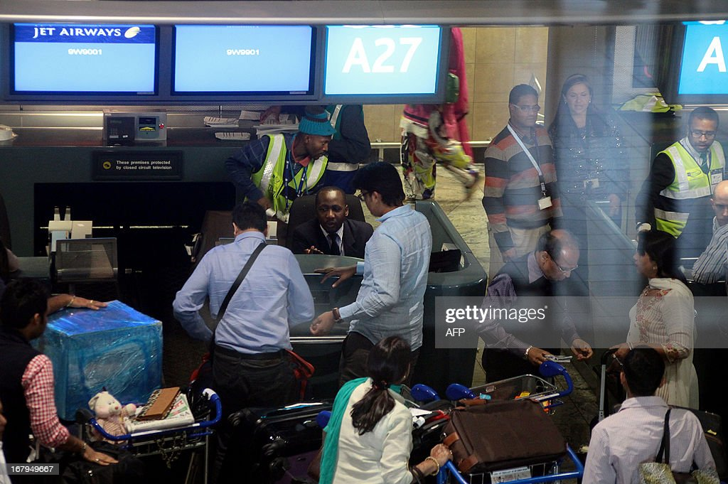The Gupta family and wedding guests check in at O. R. Tambo International Airport in Johannesburg for their flight back to India on May 3, 2013. The Gupta wedding made headlines after a plane carrying 180 wedding guests including Bollywood stars and Indian government ministers landed at Waterkloof Airforce Base in Pretoria and the guests were subsequently escorted by South African police to Sun City where the four-day wedding was to be held. Three South African government officials have since been suspended due to the incident. AFP PHOTO /JENNIFER BRUCE