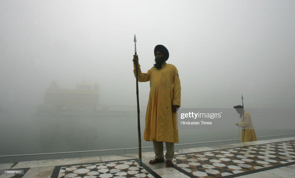 The Gurudwara taskforce men standing as of fog enveloped Sanctum of Harmandar Sahib (Golden Temple) Complex on December 24, 2012 in Amritsar, India. Heavy fog in the region causes several flights and trains delayed.