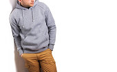 the guy in the blank grey hoodie, sweatshirt, stand, smiling on a white background, mock up, free space, template for print,  design