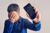 The guy is holding a black smartphone with a broken display. Broken screen of modern frameless phone. guy crying with his eyes closed and hands in his face.