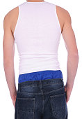 The back side of a man wearing low rise jeans showing blue boxer shorts on a white background.