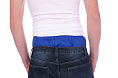 The backside of a man wearing low rise jeans showing blue boxer shorts on a white background.