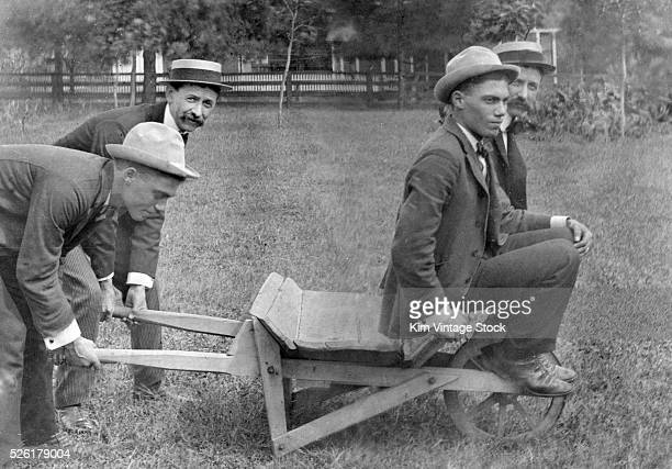 The guys play around with a wooden wheelbarrow ca 1905