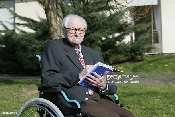 Michel Tissier Michel TISSIER ancien combattant de la guerre 1418 assis dans un fauteuil roulant un cahier à la main dans un jardin