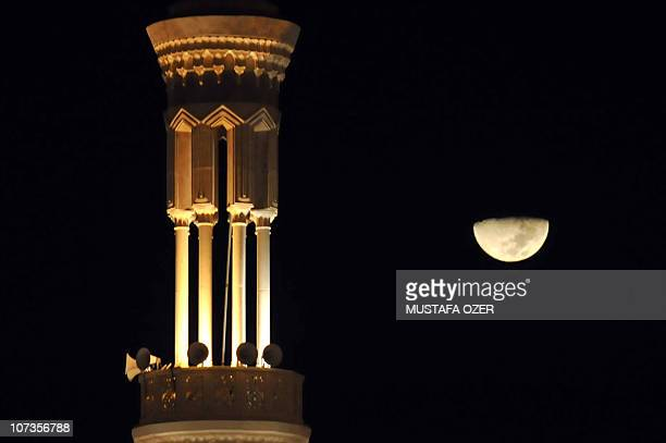 The half moon is seen behind the minaret of the Namira Mosque at Mount Arafat near the Saudi Arabian holy city of Mecca on November 14 as some 25...