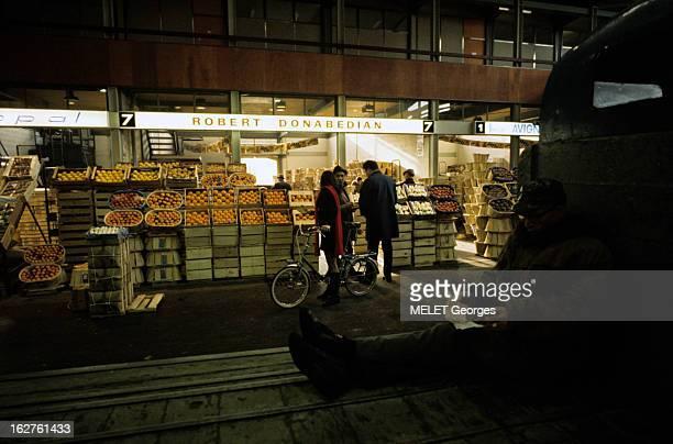 The Halls Of Rungis En France à Rungis en janvier 1970 dans les halles du marché une homme assis au sol tenant des feuille de papier au fond un...