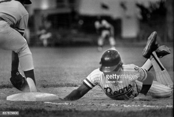 The Hand is Quicker Than the Glove Denver Bear Chet Lemon dives back to first base ahead of pickoff attempt and beats tag by Evansville's Ed Kurpiel...