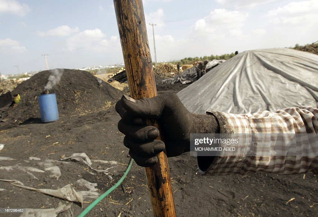 The hand of a Palestinian worker covered in soot from coal is seen holding his spade at one of the few local charcoal manufacturing plants east of Gaza City on April 23, 2013.