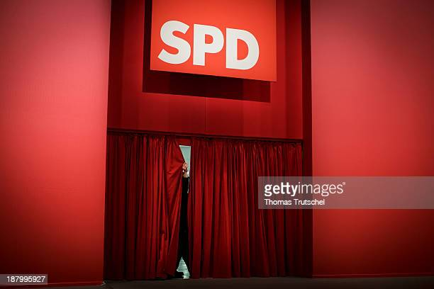 The hand of a security agent is seen behind a red curtain during the German Social Democrats party congress on November 14 2013 in Leipzig Germany...