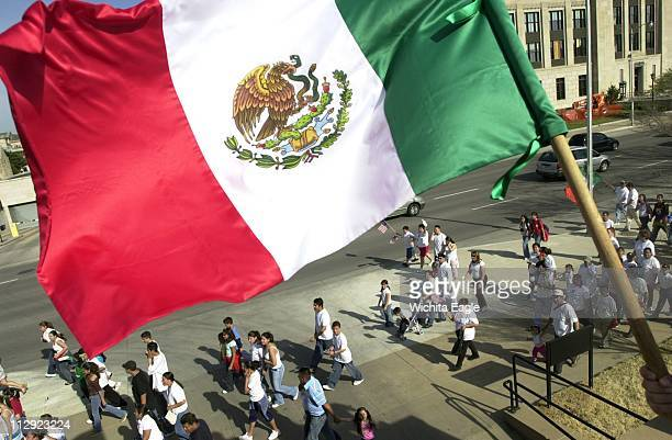 The hand of Jesus Gallego waves a Mexican Flag as marchers walk back to the Wichita City Hall Building during the National Day of Action in Wichita...