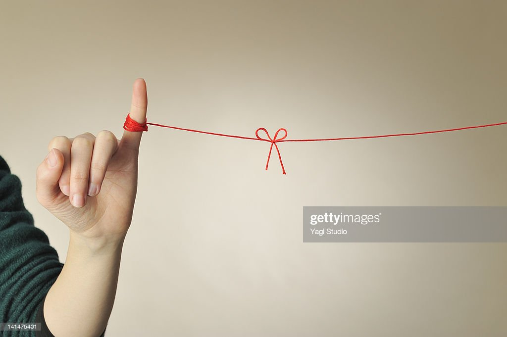 The hand of the woman connected with a red thread