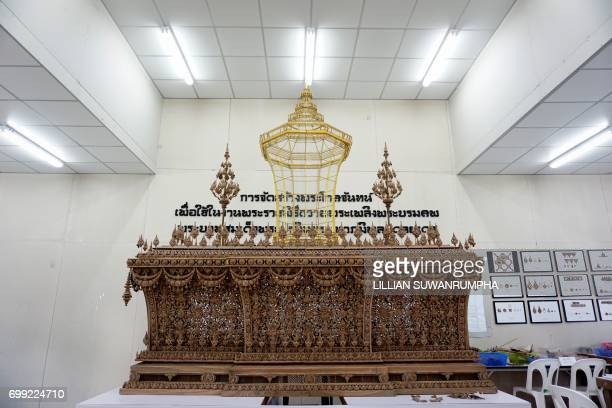 The handcarved wooden urn is seen under construction in a warehouse near the funeral pyre and surrounding pavilions for the late Thai King Bhumibol...