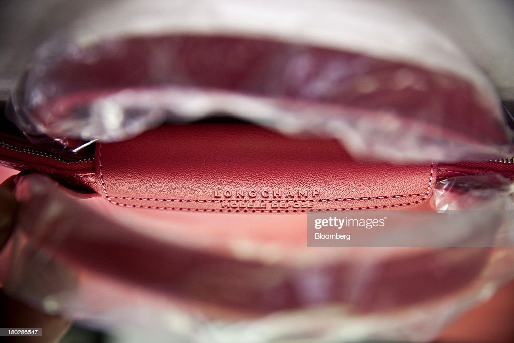 The handle of a finished a Le Pliage Cuir bag is wrapped in protective plastic at the Longchamp SAS workshop in Segre, France, on Monday, Sept. 9, 2013. Longchamp SAS, the French handbag maker, which is known for foldable Le Pliage nylon tote bags, expects sales in China to rise, Chief Executive Officer Jean Cassegrain said. Photographer: Balint Porneczi/Bloomberg via Getty Images