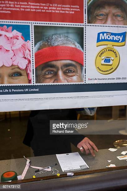 The hands and fingers of an anonymous customer is seen through a city Post Office window behind a pension savings ad Three faces of models used for...