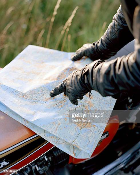 The hands of a motorcyclist reading a map.