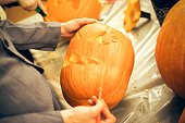 The hands of a student shown carving a face into a pumpkin with a thin knife other pumpkins surrounding Halloween at Johns Hopkins University's...