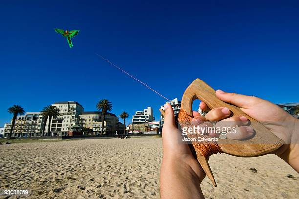 The hands of a young boy flying a bright green Balinese dragon kite.