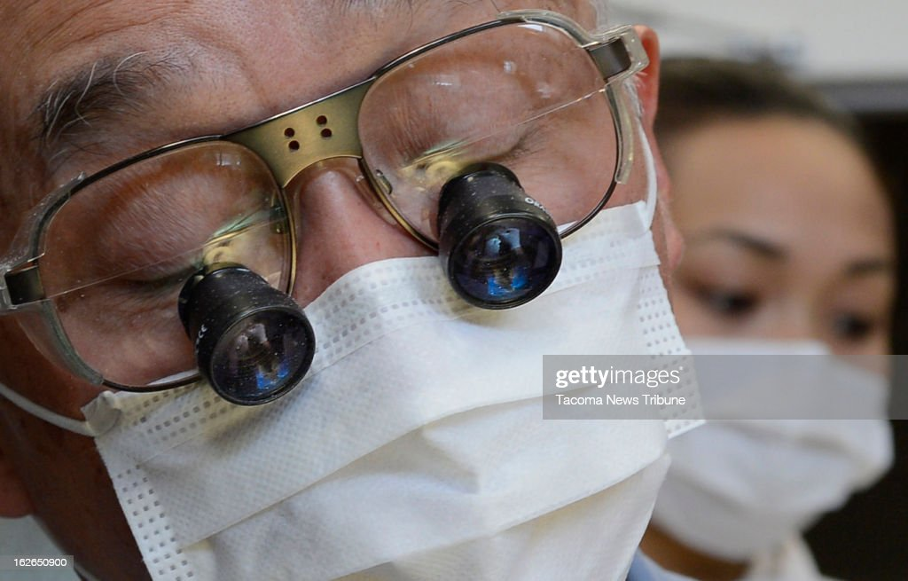 The hands of Dr. Edmund Kwan, from Tukwila, are reflected in the special eye-piece he used as he performed a root canal on Boris the Polar Bear on Saturday, February 23, 2013 at the Point Defiance Zoo & Aquarium's animal health care hospital in Tacoma, Washington.