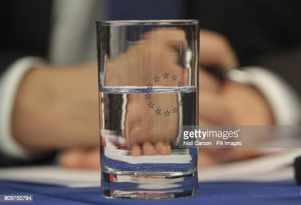 The hands of Istvan Szekely of the European Commission are seen through a glass of water as he speaks to the media at a press conference on the...