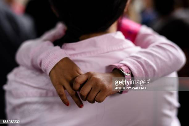 The hands of Keana daughter of Filipino refugee Vanessa Rodel are seen as she hugs her mother outside the Immigration Tower in Hong Kong on May 15...