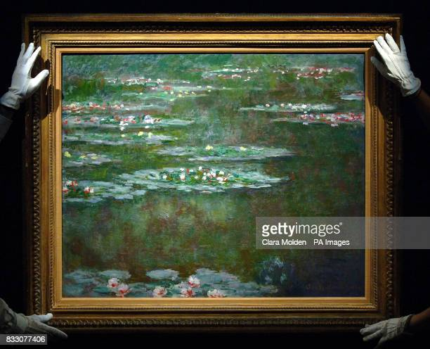 The hands of Sothebys technicians are seen holding 'Nympheas' by Claude Monet at Sothebys auction house in London