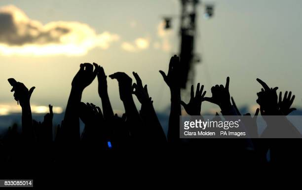 The hands of the crowd are seen silhouetted against the evening sky as Faithless perform on the Main Stage at the O2 Wireless Fesival in Hyde Park...