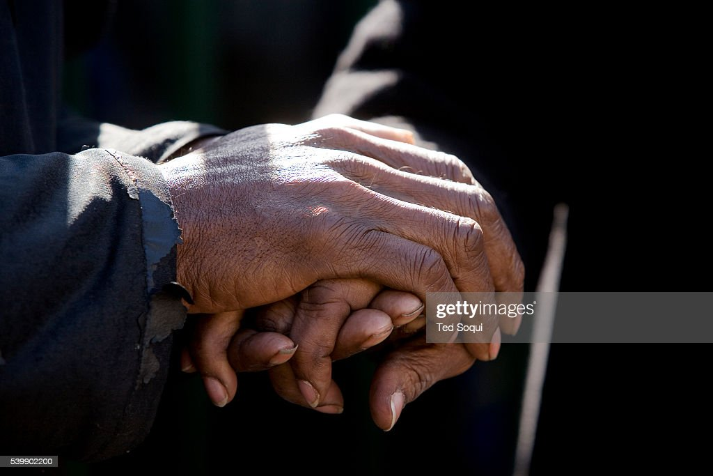 the hands of the homeless join together in a prayer for