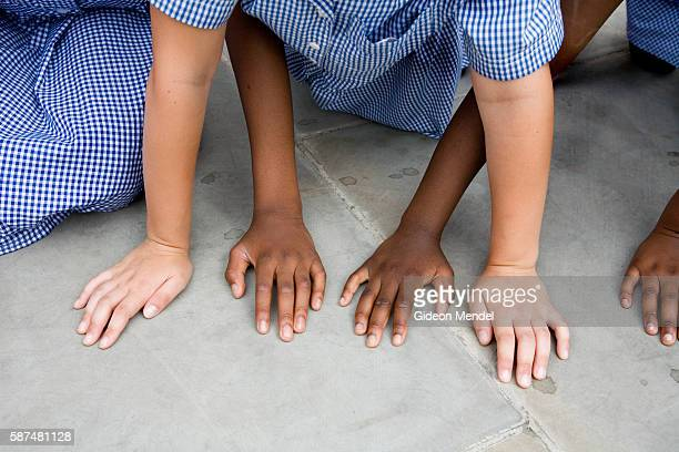 The hands of two schoolgirlds from Millfields Community School placed on the ground as their class plays a coordination game This was during a class...