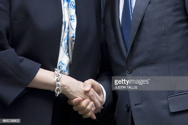 The handshake between British Prime Minister Theresa May and European Council President Donald Tusk is pictured outside 10 Downing street in central...