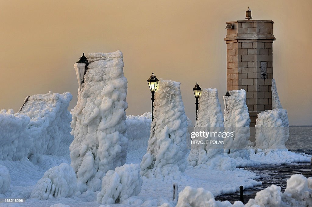 The harbour breakwater with lighthouse and lampposts is covered with heavy ice in the central Adriatic Croatian port of Senj, some 200 kilometres from Zagreb, as the sun sets on February 8, 2012. Europeans across the continent have been battling more than a week of extreme weather with more than 100 villages still trapped by snow in remote, mountain parts in Croatia and several dead by freezing as temperatures hit more than 20 Celsius below zero. The new deaths put the toll for the Balkans up to 23 from which three of them in Croatia. AFP PHOTO/ Hrvoje POLAN
