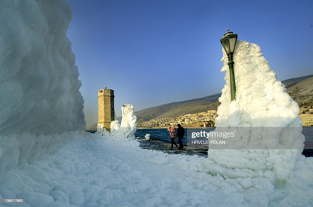 The harbour's breakwater with lighthouse and lampposts is covered with heavy ice in the central Adriatic port of Senj, some 200 kilometres from Zagreb, as the sun sets on February 8, 2012. Europeans across the continent have been battling more than a week of extreme weather with more than 100 villages still trapped by snow in remote, mountain parts in Croatia and several dead by freezing as temperatures hit more than 20 Celsius below zero. The new deaths put the toll for the Balkans up to 23 from which three of them in Croatia. AFP PHOTO/ Hrvoje POLAN