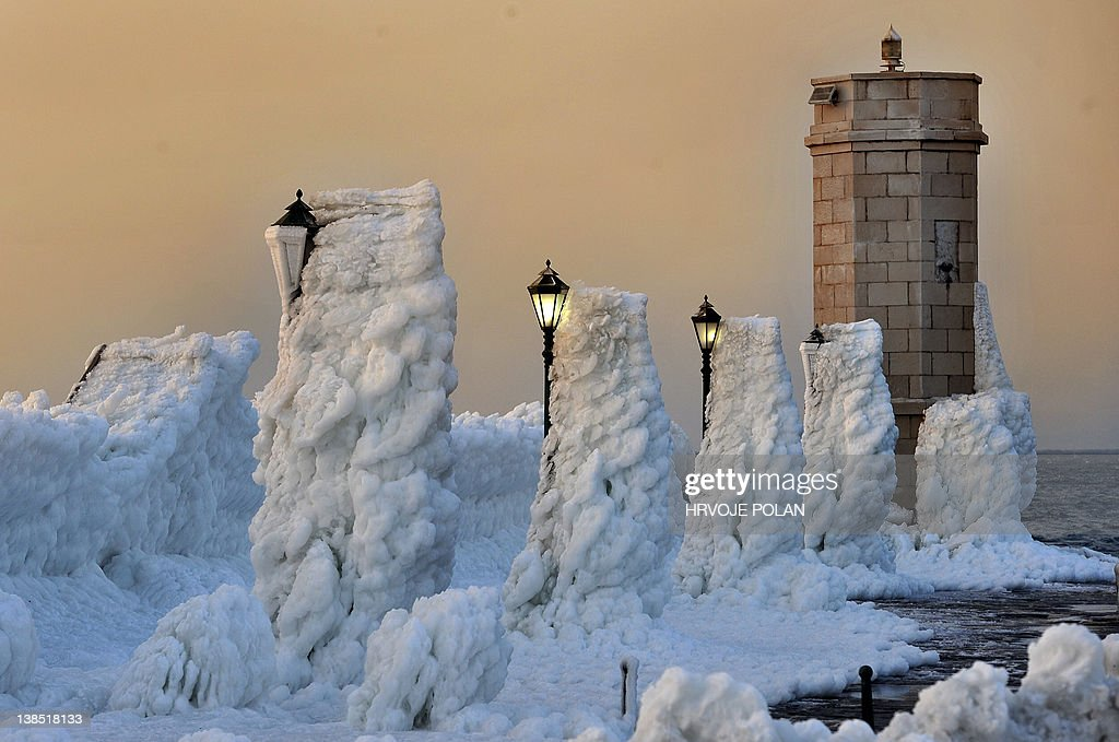 The harbour's breakwater with lighthouse and lampposts is covered with heavy ice in the central Adriatic Croatian port of Senj, some 200 kilometres from l Zagreb, as the sun sets on February 8, 2012. Europeans across the continent have been battling more than a week of extreme weather with more than 100 villages still trapped by snow in remote, mountain parts in Croatia and several dead by freezing as temperatures hit more than 20 Celsius below zero. The new deaths put the toll for the Balkans up to 23 from which three of them in Croatia. AFP PHOTO/ Hrvoje POLAN