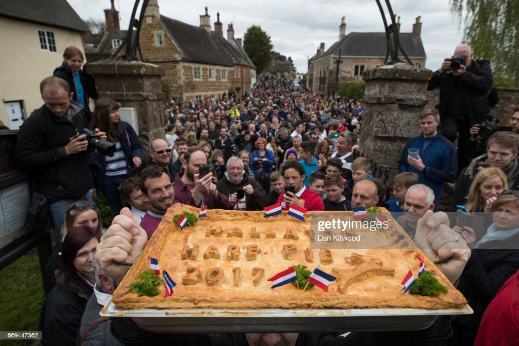The hare pie is blessed by the vicar after being carried through the village on April 17, 2017 in Hallaton, England. Hallaton hosts the Hare Pie Scramble and Bottle Kicking event today. The Bottle Kicking follows the Hare Pie Scramble, two events that are combined to form an ancient custom that dates back to the early eighteenth century, and one of the oldest in British History. The first part consists of a blessing of a Hare Pie by a local vicar, before it is cut up and thrown to the crowd, who 'scramble' to get a piece, believing it will bring good luck. The second part, the Bottle kicking sees two rival villages, Hallaton, and neighboring Medbourne attempt to carry a 'bottle' which is actually a keg of beer, from the Hare Pie Bank, and get it across a boundary stream for their own village. The best of three contest can last several hours.