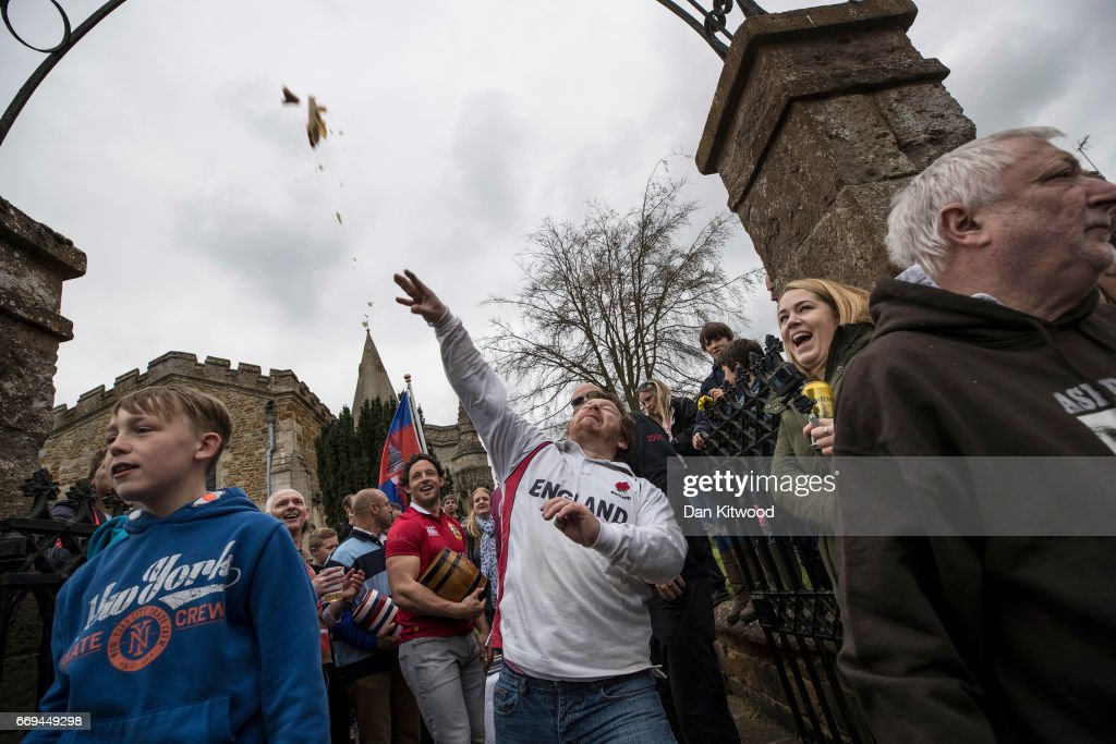 The hare pie is thrown to the crowd after being carried through the village on April 17, 2017 in Hallaton, England. Hallaton hosts the Hare Pie Scramble and Bottle Kicking event today. The Bottle Kicking follows the Hare Pie Scramble, two events that are combined to form an ancient custom that dates back to the early eighteenth century, and one of the oldest in British History. The first part consists of a blessing of a Hare Pie by a local vicar, before it is cut up and thrown to the crowd, who 'scramble' to get a piece, believing it will bring good luck. The second part, the Bottle kicking sees two rival villages, Hallaton, and neighboring Medbourne attempt to carry a 'bottle' which is actually a keg of beer, from the Hare Pie Bank, and get it across a boundary stream for their own village. The best of three contest can last several hours.
