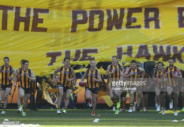 The Hawks break through the banner during the round 12 AFL match between the Hawthorn Hawks and the Gold Coast Suns at Melbourne Cricket Ground on...