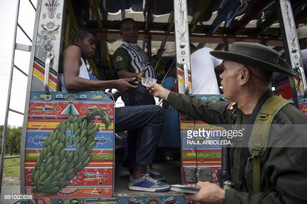 The head of Colombia's antinarcotics police Jose Mendoza hands out pamphlets offering rewards for information leading to the capture of members of...