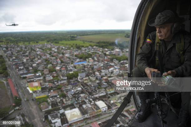 The head of Colombia's antinarcotics police Jose Mendoza throws pamphlets from a helicopter offering rewards for information leading to the capture...