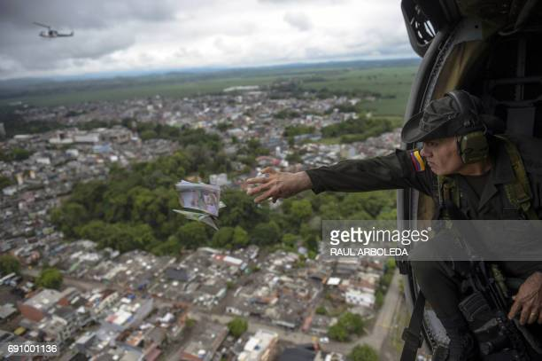 TOPSHOT The head of Colombia's antinarcotics police Jose Mendoza throws pamphlets from a helicopter offering rewards for information leading to the...