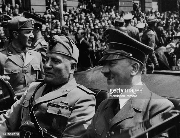 The head of Fascist government Mussolini sitting on a car next to the Fuehrer of the Third Reich Adolf Hitler 1930s