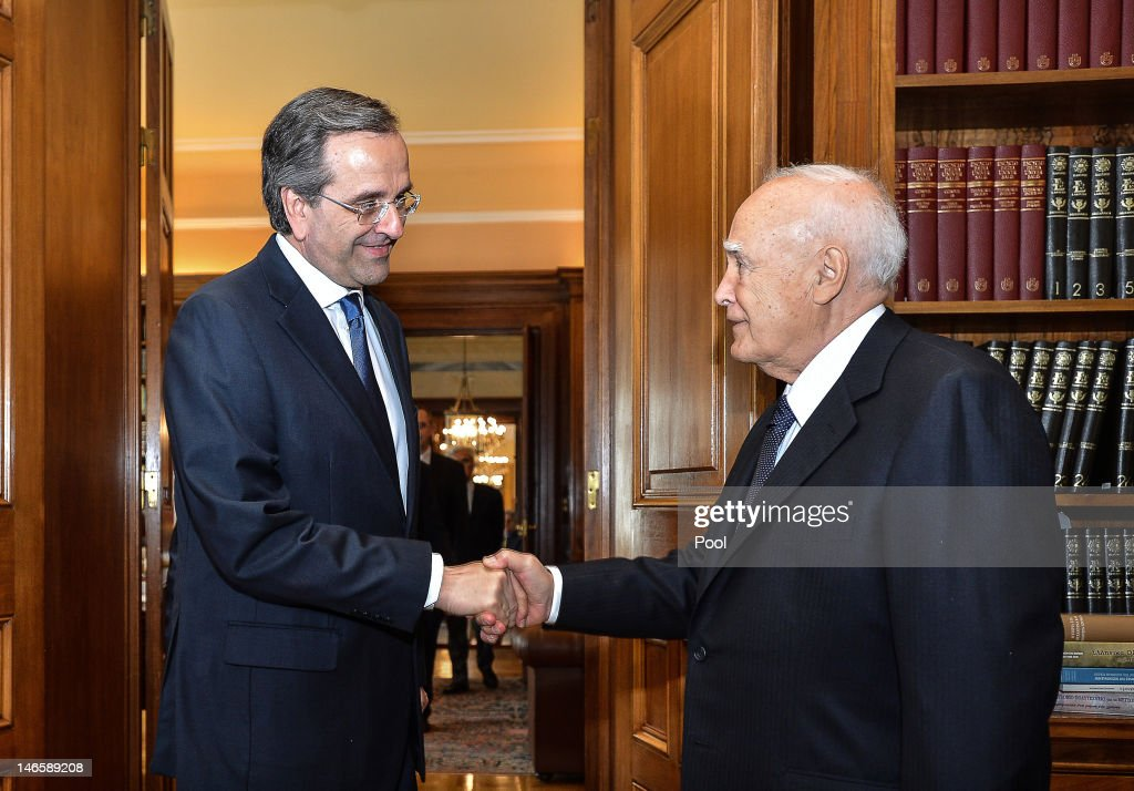 The head of Greece's conservative New Democracy party, Antonis Samaras (L) shakes hands with Greek President Karolos Papoulias at the presidential palace on June 20, 2012 in Athens, Greece. Samaras pledged to pull his debt-stricken country back from the brink of bankruptcy in his first comments after being sworn in as Greek Prime Minister.