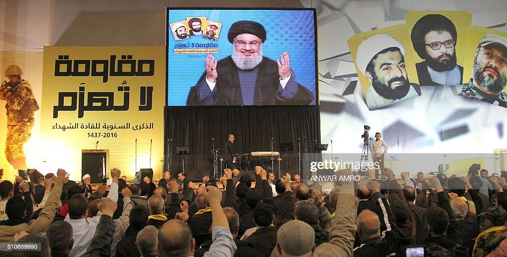 The Head of Lebanon's Shiite movement Hezbollah Hassan Nasrallah is seen on a giant screen as he addresses the crowd in a televised speech from an...