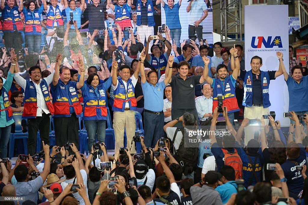 The head of opposition party, current vice-president and presidential candidate Jejomar Binay (C, in blue shirt), along with his senatorial line up led by boxing icon Manny Pacquiao (3rd R) raise their hands during their proclamation rally in Manila on February 9, 2016. A cliffhanger race to lead the Philippines began February 9 with emotion-charged rallies by a dead movie star's adopted daughter, a politician who brags about killing criminals and other top contenders. AFP PHOTO / TED ALJIBE / AFP / TED ALJIBE