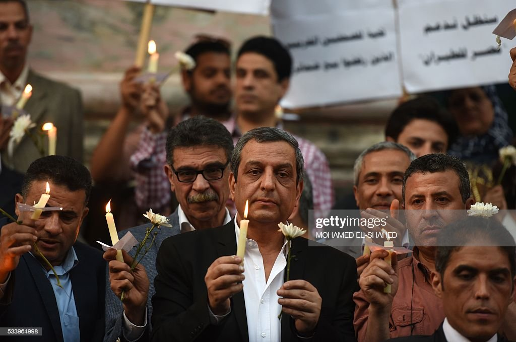The head of the Egyptian journalists union, Yahiya Kallash(C), stands among colleagues during a candle light vigil in memory of EgyptAir MS804 victims in front of the Journalists' Syndicate in Cairo on May 24, 2016. The Airbus A320 carrying 66 people had crashed into the sea while flying from Paris to Cairo early May 19, 2016, and some wreckage but not the black boxes has been found. SHAHED
