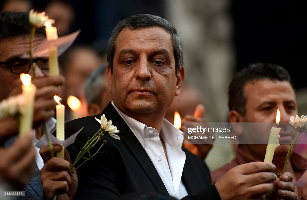 The head of the Egyptian journalists union, Yahiya Kallash (C), stands among colleagues during a candle light vigil in memory of EgyptAir MS804 victims in front of the Journalists' Syndicate in Cairo on May 24, 2016. The Airbus A320 carrying 66 people had crashed into the sea while flying from Paris to Cairo early May 19, 2016, and some wreckage but not the black boxes has been found. SHAHED